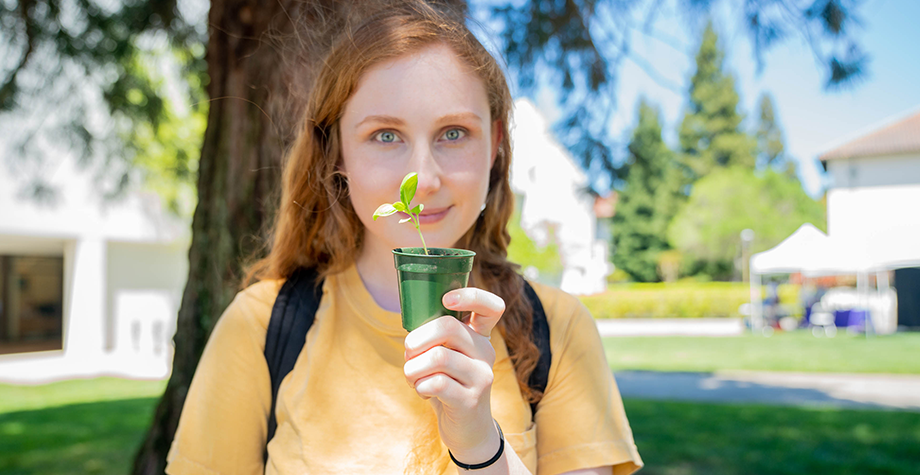 Student holds a small green plant