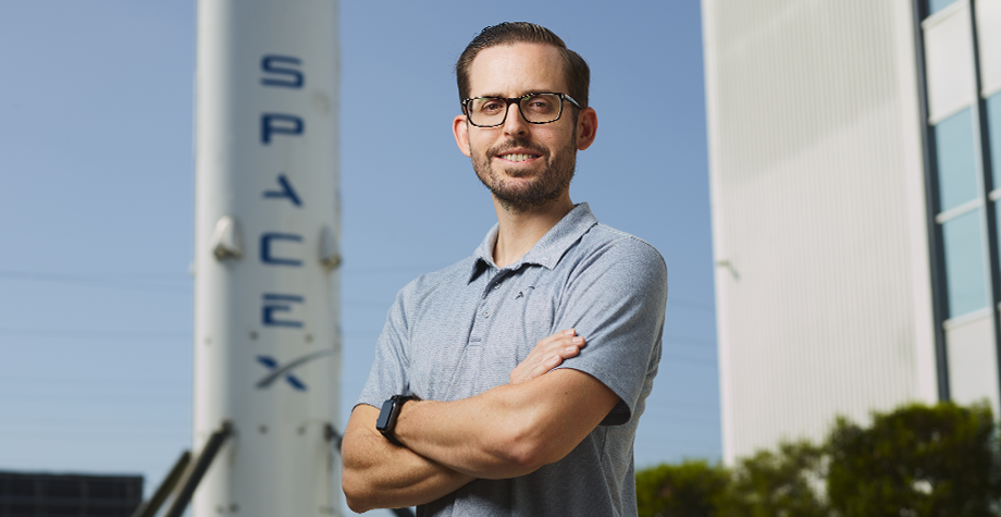 alum Alex stilling poses in front of SpaceX