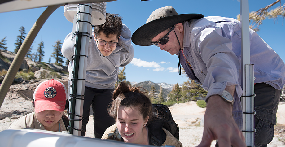 Summer researchers gather around an ozone measurement tool