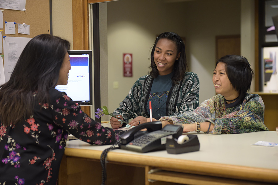 Two students are helped by an employee in Human Resources.