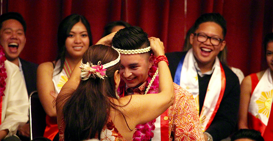 graduating senior is honored with  a tradtional Asian Pacific head-dress from a family member