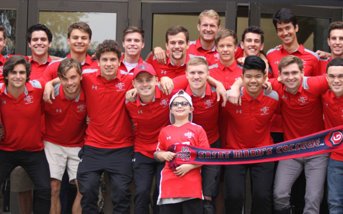 Men's soccer team poses with Quentin Rios