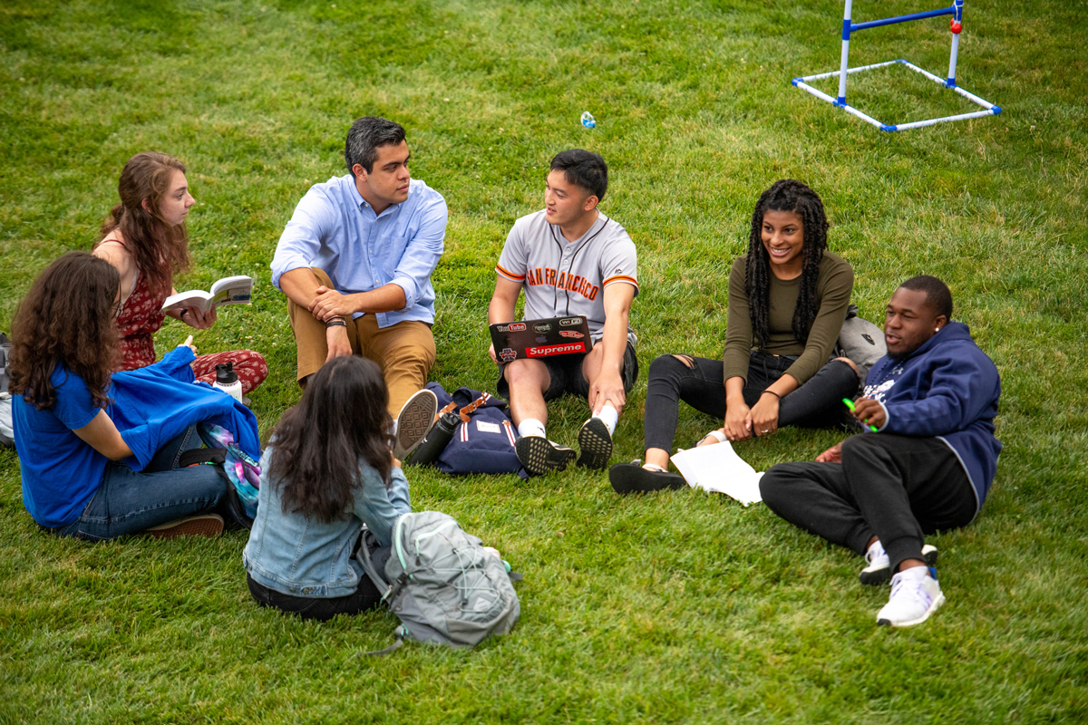 Students sitting in a circle on the grass talking