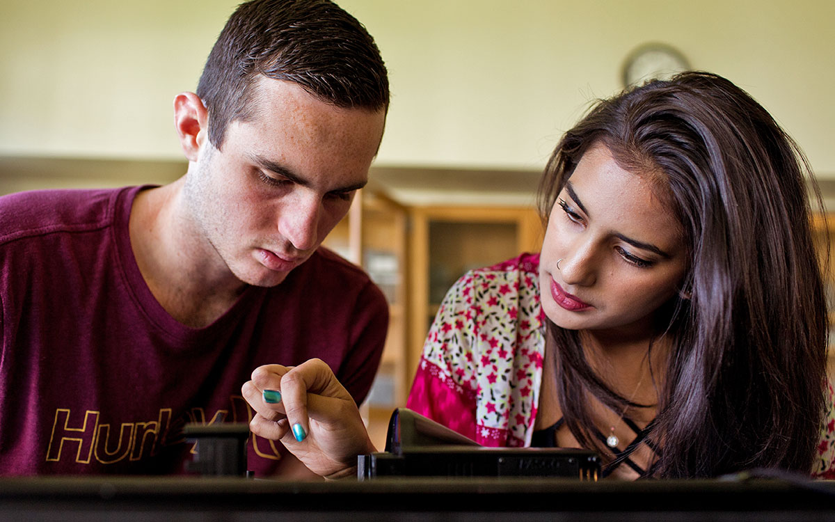 A male and female student work together in a classroom.