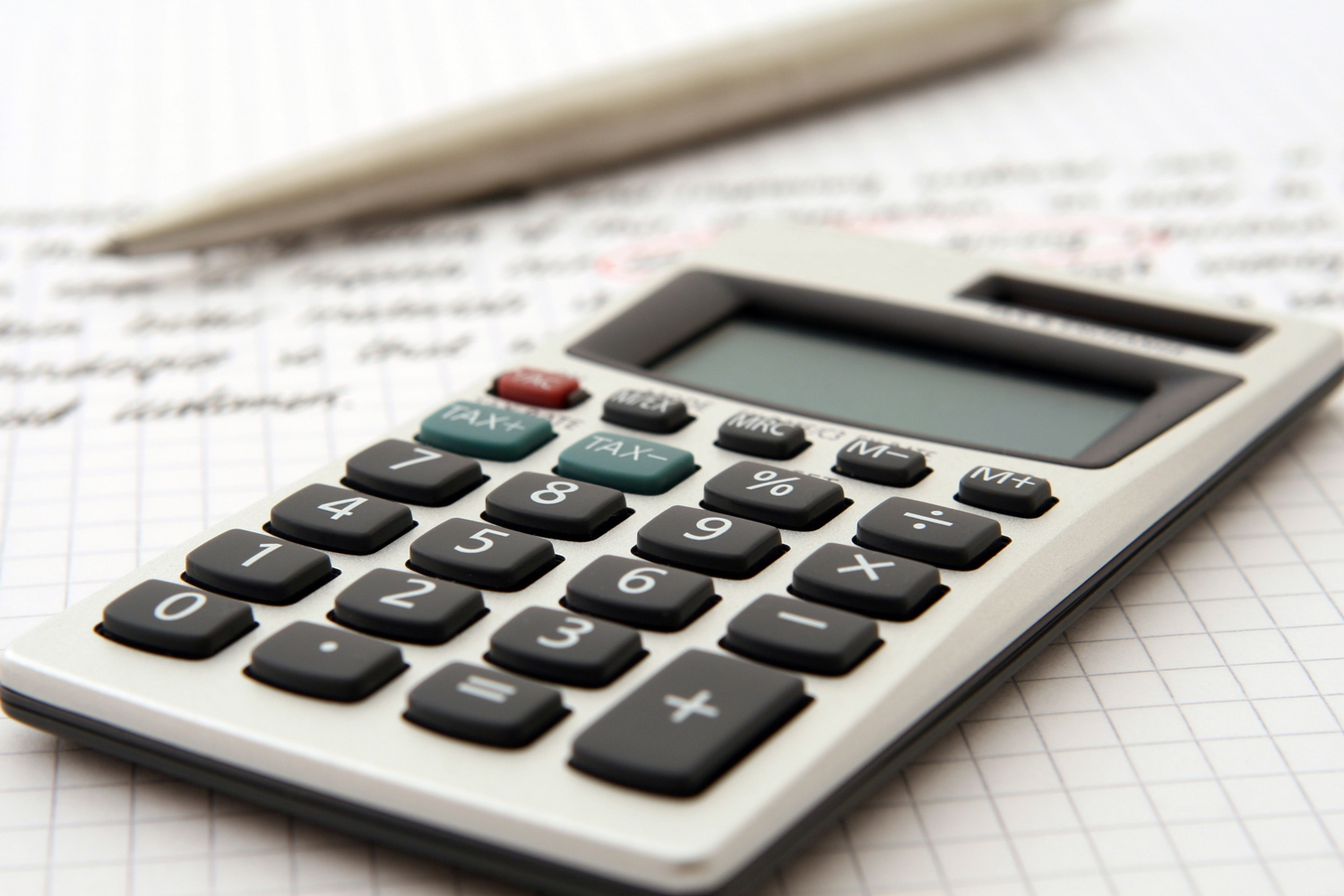 A close of of a calculator with a balance sheet
