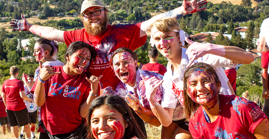 6 students pose with blue and red paint splatters while painting the SMC