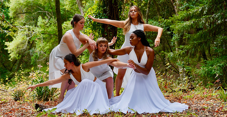 Five women perform a dance in white dresses in the forrest