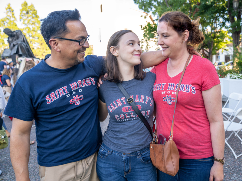 A Saint Mary's student between her mother and father, all wearing Saint Mary's College shirts.