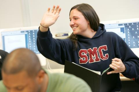 A student in an SMC sweatshirt raises her hand