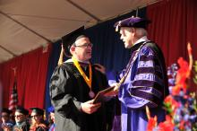 An older graduate in cap and gown receives his diploma