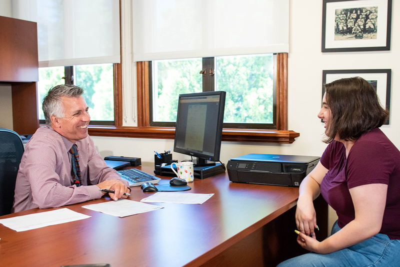A student sitting at a desk during a meeting with an admissions counselor who is answering question.